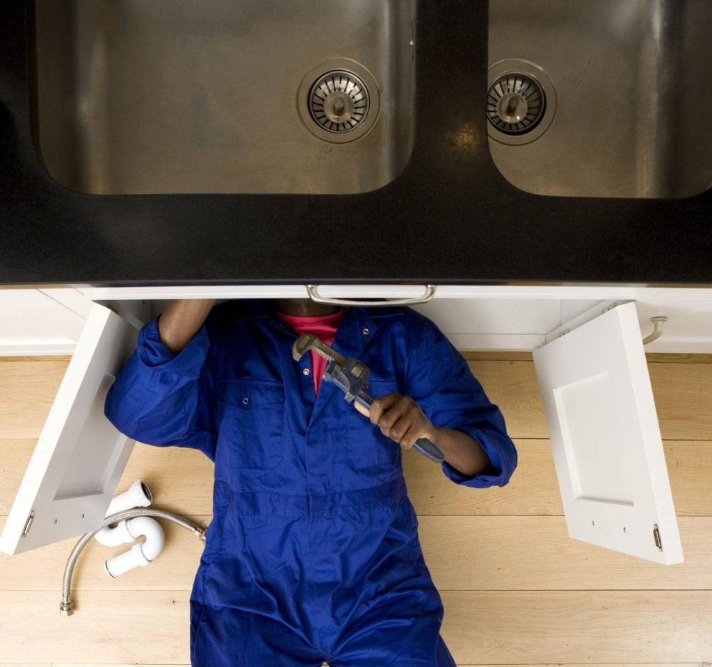 idraulico che mette a posto rubinetto, tubature, impianto acqua